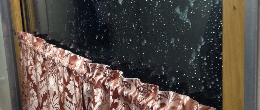 Flecks of iced water on a dark window.
