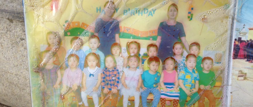 Class photo shows a group of small children and two teachers in blue dresses.