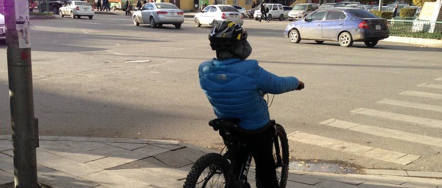 A young boy on a mountain bike waits to cross a zebra crossing.