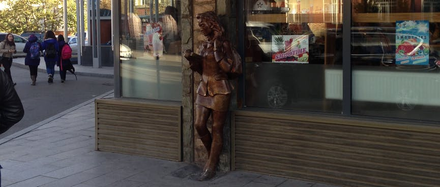 A bronze statue reads a book, outside the Uni Coffee House.