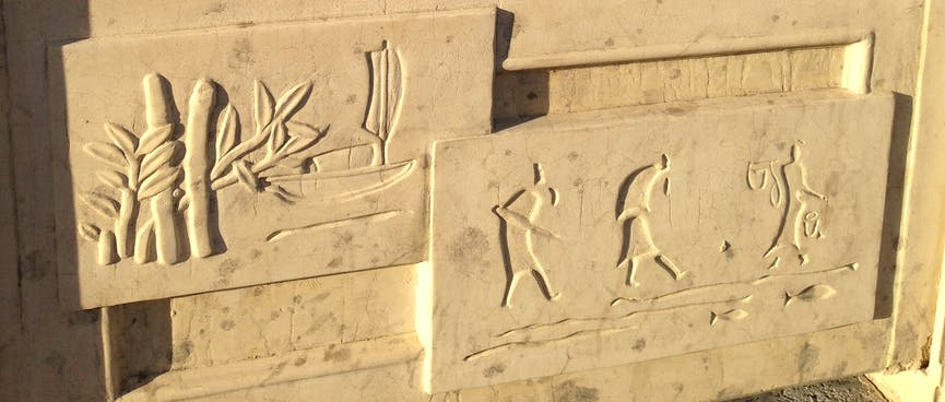Tall apartment buildings going up next to vacant lots. In the foreground, ancient scenes carved into a stone railing.