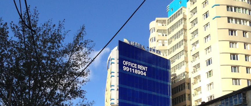 A high rise has a sign for 'Office Rent'.