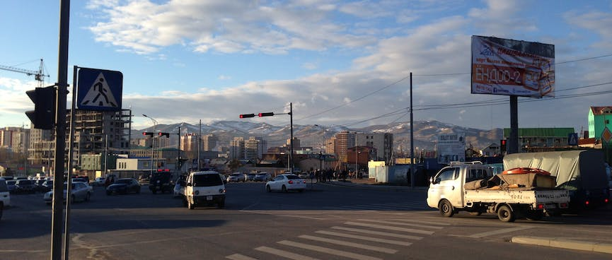 Views of apartment buildings and snowy mountains at a busy intersection.