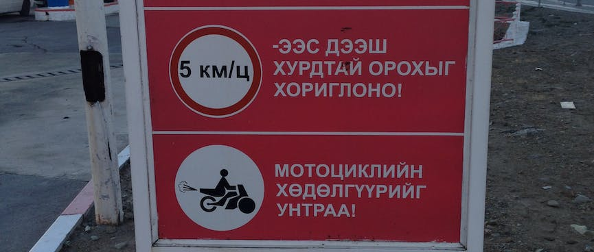 Sign at a petrol station depicts 5 km/h speed limit and a speeding motor scooter.