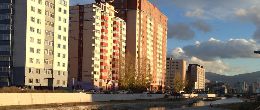 Tall apartment buildings on the edge of a gentrified river.