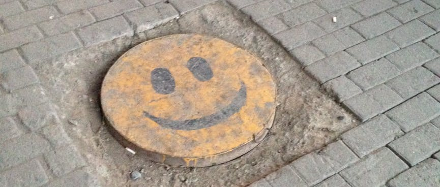 A manhole cover is painted with a yellow smiley face.