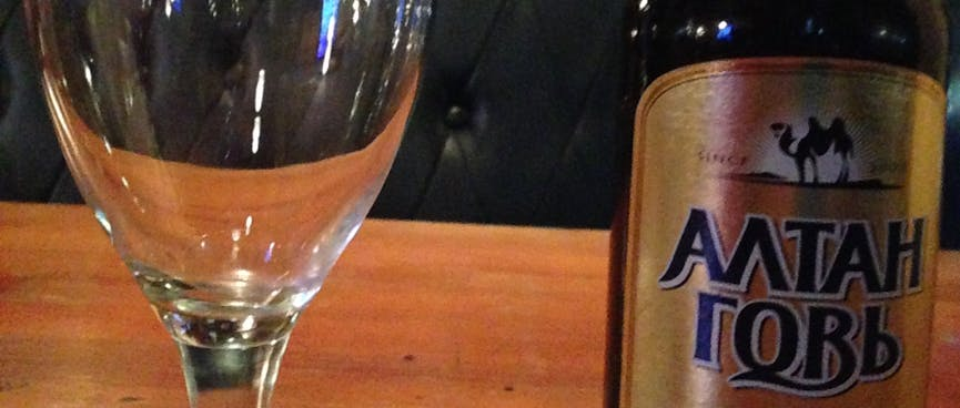 Bottle of beer and beer glass in front of an empty booth bench.