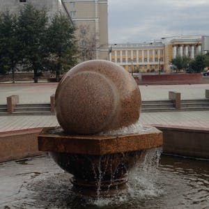 View enlargement of A large granite kugel ball spins on top of a water fountain, in Chita.