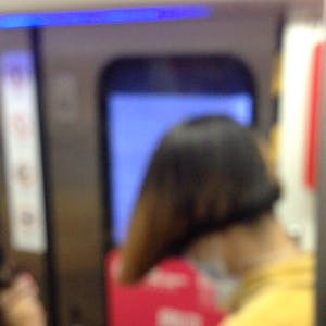 View enlargement of Ads for sports clothing are projected onto the tunnel wall in a Beijing subway.