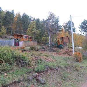 View enlargement of Wooden houses set into the forest.