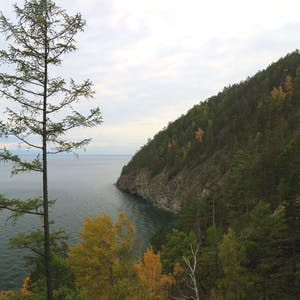 View enlargement of A forested hill ends in rocky walls rising from the lake.