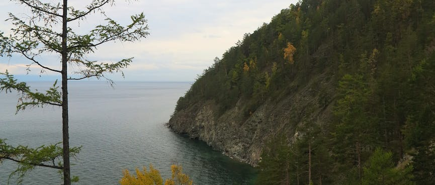 A forested hill ends in rocky walls rising from the lake.