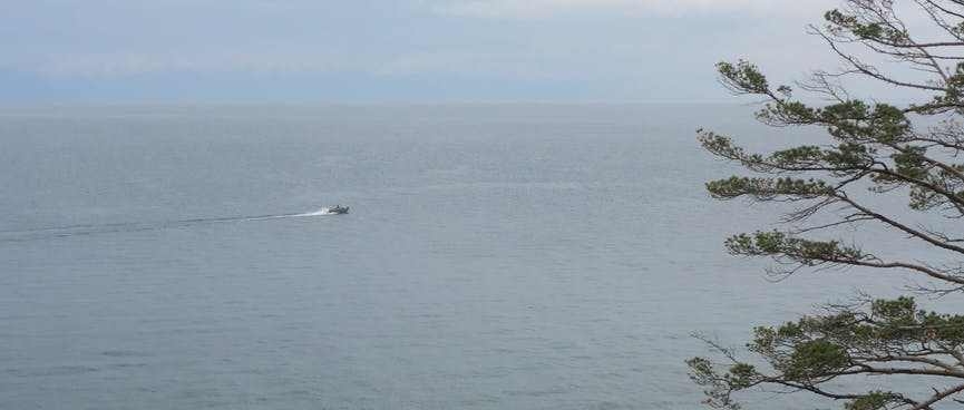 A small boat, maybe 100m offshore.