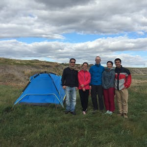 View enlargement of Five people stand next to a tent.