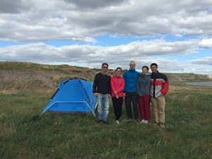 Five people stand next to a tent.