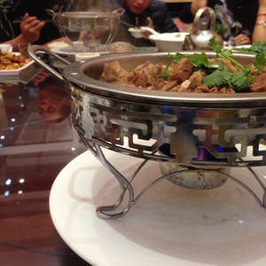 View enlargement of People eat after serving themselves from a heated metal dish filled with meat.