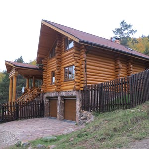 View enlargement of Double garage below a large log house.