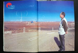 A two page magazine spread shows a sketches of modern infrastructure overlaid on a barren steppe.