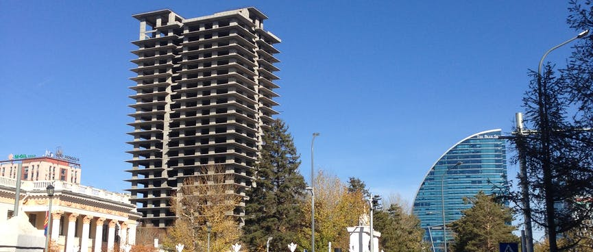 Rectangle and circular high rises soar above low rise buildings.