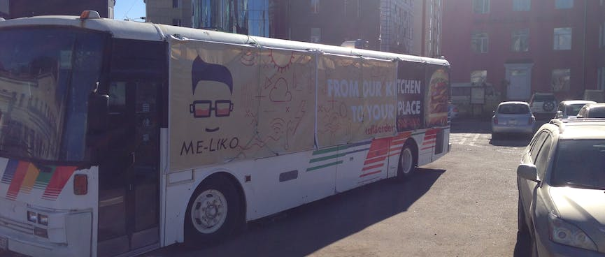 Advertising for the Me-liko food catering service is draped over the windows of a bus.