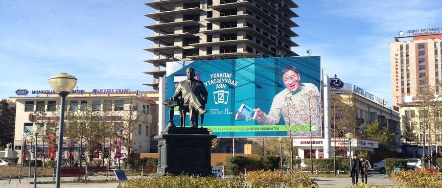 A man on a billboard seems to reach out towards a metal statue of a man in a chair.