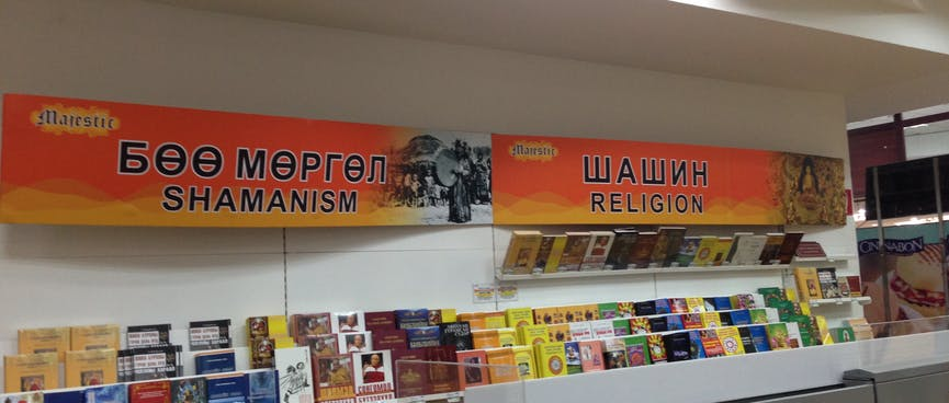 Two halves of a book shelf are signposted with 'Shamanism' and 'Religion'.
