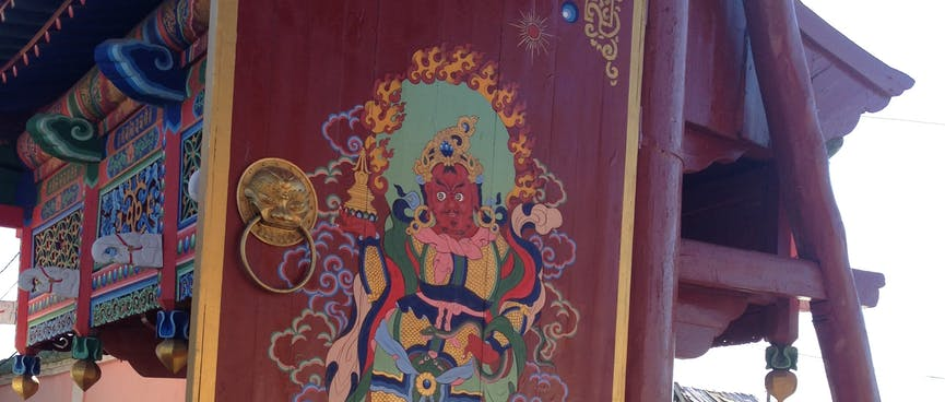 An ornate wooden painting of a dark skinned god wearing a pink scarf.