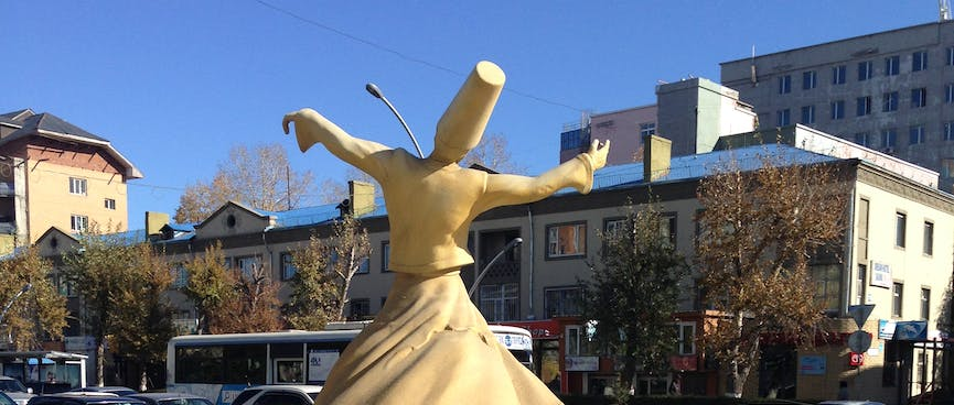 A cream statue of a dancing man wearing a long skirt and a tall hat.