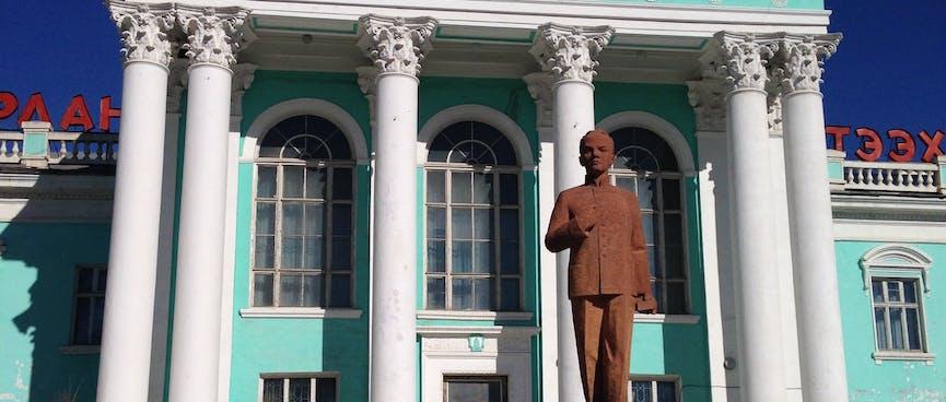 A bronze statue of a standing man wearing a dress jacket with a mandarin collar.