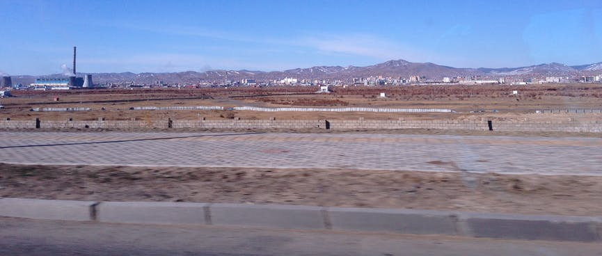 Empty steppes, a power plant and in the distance city buildings and low mountains.