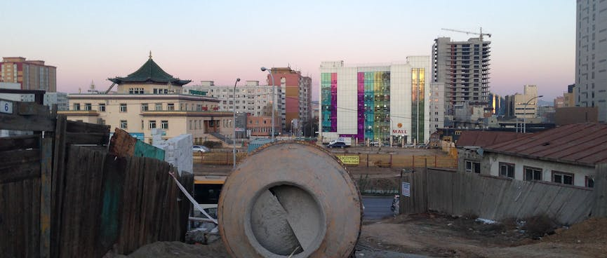 A concrete mixer stands on an empty section. In the distance the skyline is a mixture of traditional temples and garish high rises.