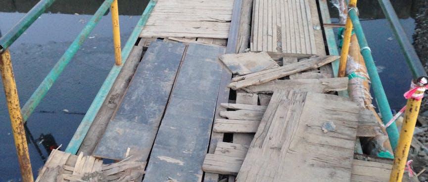 Loose bits of wood cover the metal bones of a pedestrian bridge.