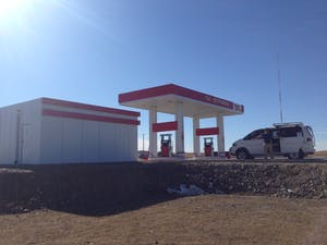 White buildings with red trim at a petrol station.