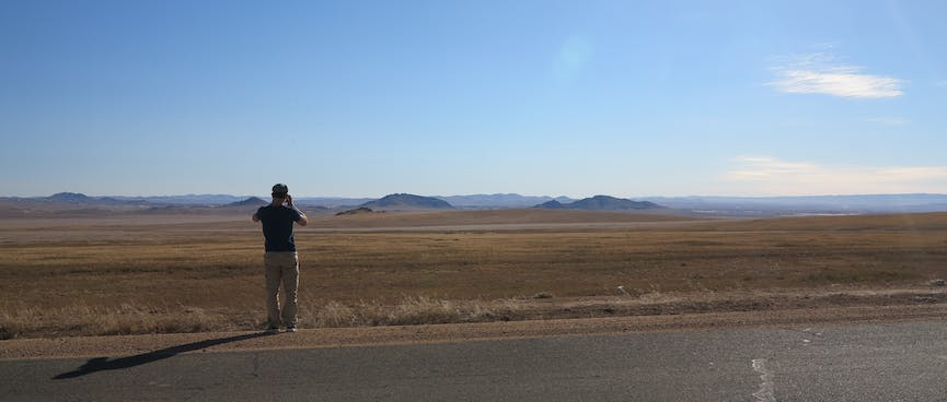 A man photographs steppes and distant hills.