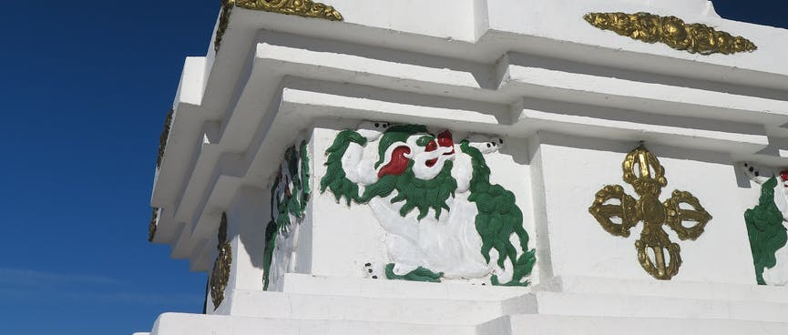 A stone monument is adorned with golden swirls and the figure of a white lion.