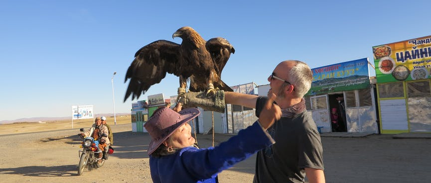A lady in a blue cloak and brown hat waves her arms to scare the eagle.