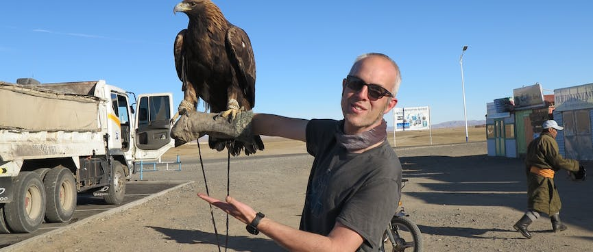 I look at the camera while an eagle perches on my forearm.
