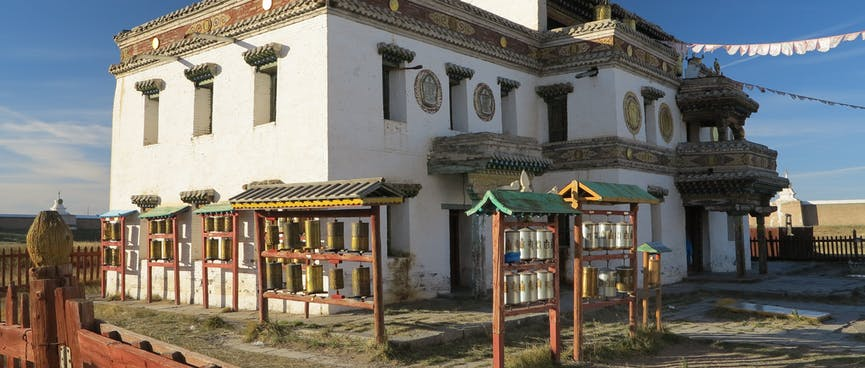 Prayer wheels and flags outside a two story stone building.