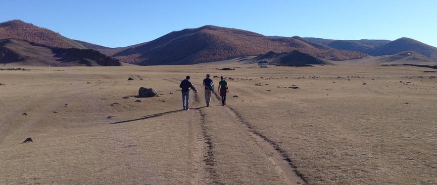 Three people walk towards the hills, following tyre tracks in the grass.