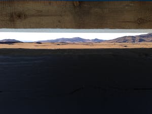 A thin slit in the toilet door provides a panoramic view of the landscape.