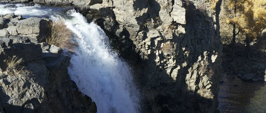 A foaming waterfall plunges down a rock face.