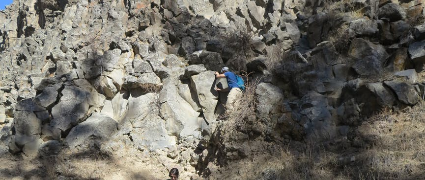Members of the tour part pick their way down the steep rocky hillside.