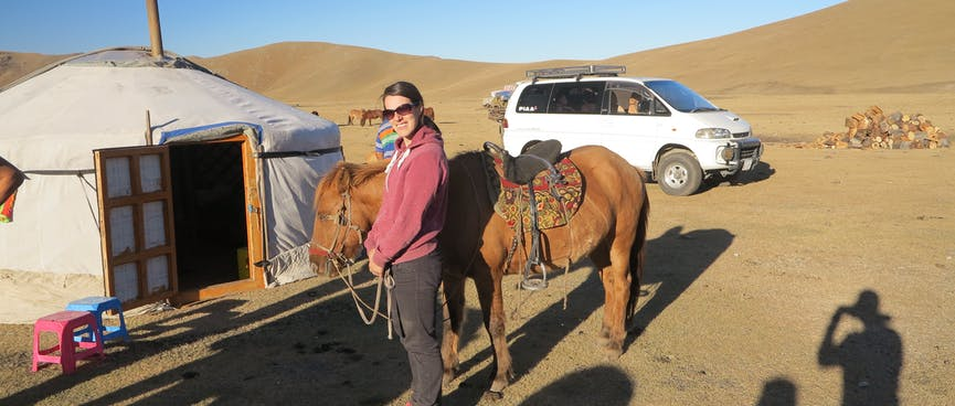 A female tourist stands next to a brown horse.