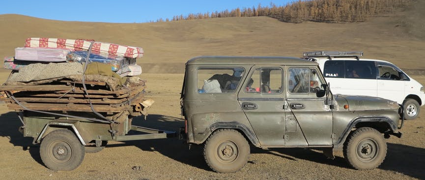 A green army jeep tows a small trailer stacked with belongings.