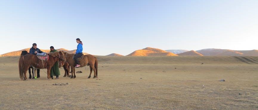 Riders adjust their horses' saddles.