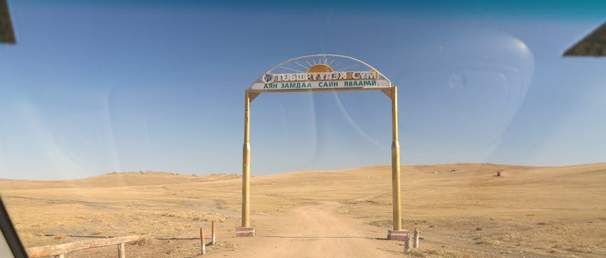 A simple wooden archway straddles a dirt road.