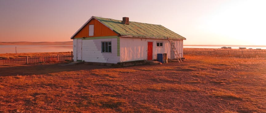 A white red and green house bathed in an orange glow.
