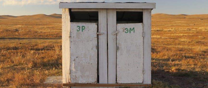 A white wooden shed with two doors.