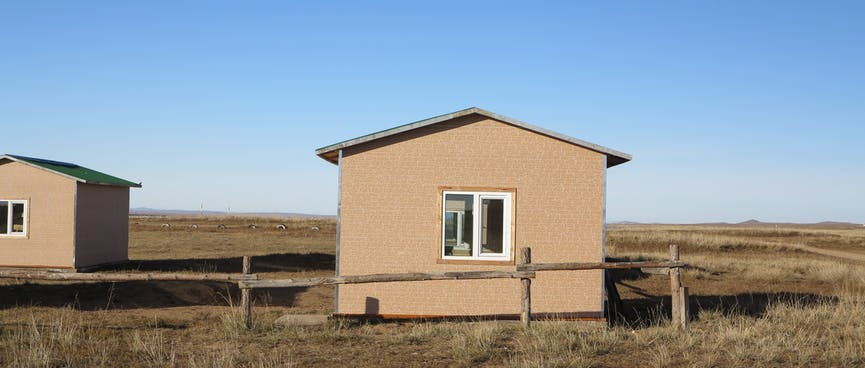 Identical windowed huts, light brown with green roofs.