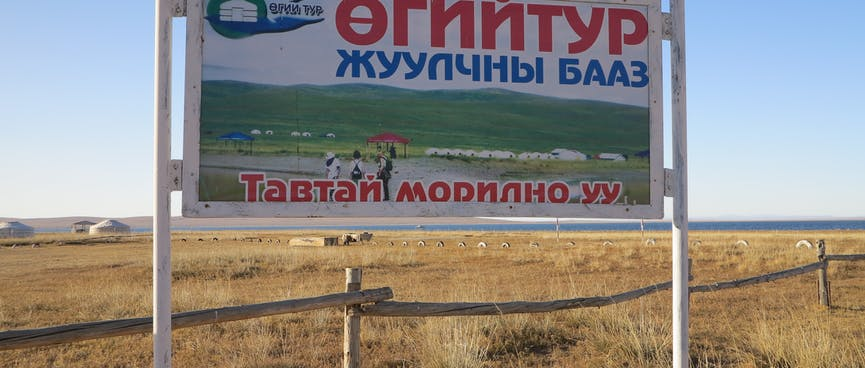 A billboard in a paddock shows white gers on a backdrop of green hills.